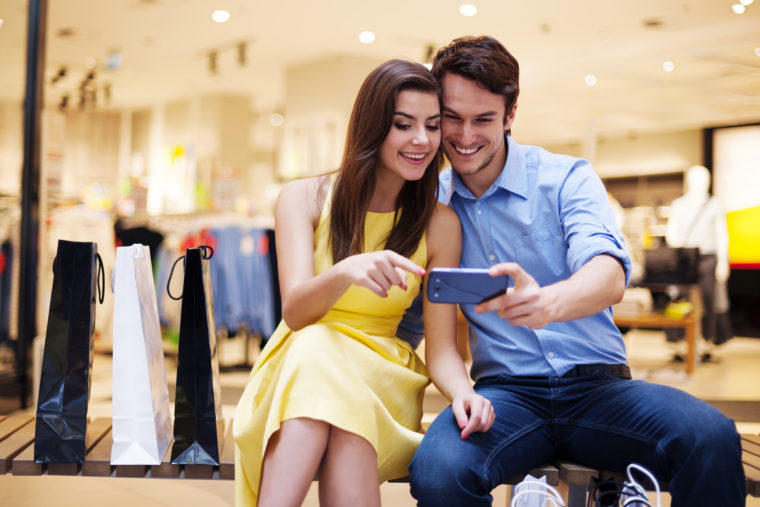 Couple-on-a-mall-bench-with-smartphone-shutterstock_138306533